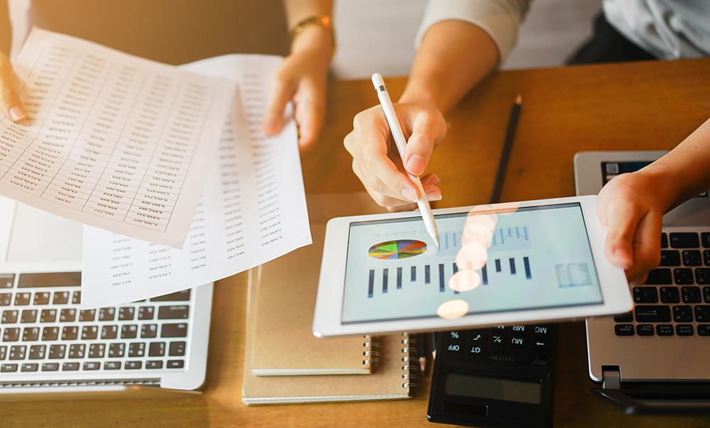 lose up group of businessman use stylus pen for explaining dashboard about company's profit monthly on tablet and businesswoman holding report paper for collaborate work at meeting event , business finance concept