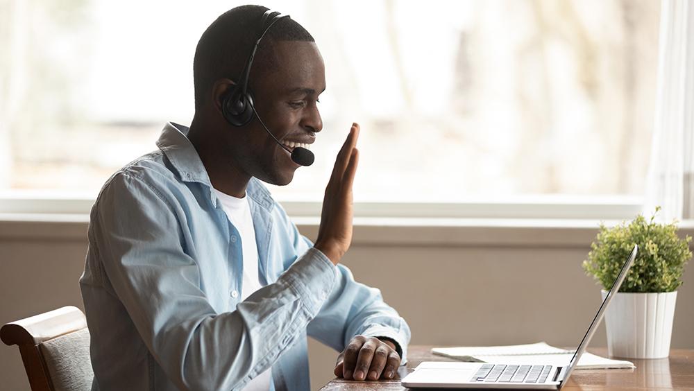 A man waving at someone on his computer